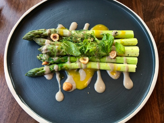 Inferno Pizzeria Napoletana tender roasted asparagus with sauces of black truffle and egg yolk, topped with crunchy hazelnuts